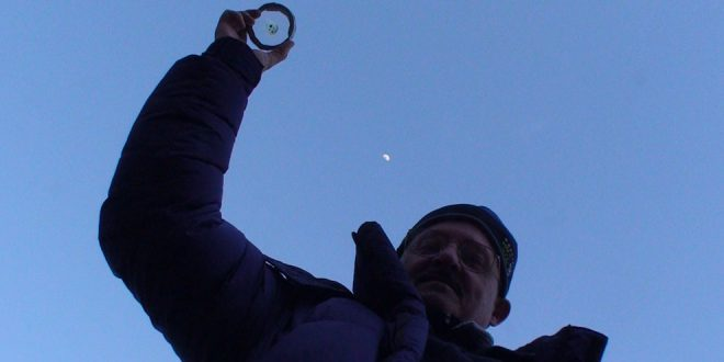 Keith holding an Apollo 11 moon rock over his head as the moon rises over Everest Base Camp