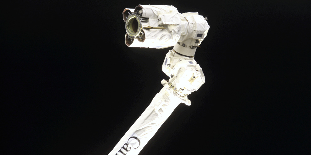 View of the end effector of the Canadarm2 / Space Station Remote Manipulator System (SSRMS) taken by a STS-108 crewmember through an aft flight deck window during the docking approach of the Space Shuttle Endeavour to the International Space Station