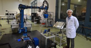 MDA's CTO Cameron Ower stands next to satellite servicing robotic technology