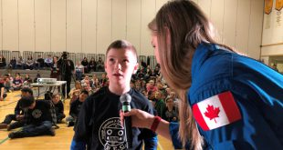 Astronaut Jenni Sidey-Gibbons holds the microphone for a student of East Three School (elementary and secondary) in Inuvik as he asks David Saint-Jacques a question