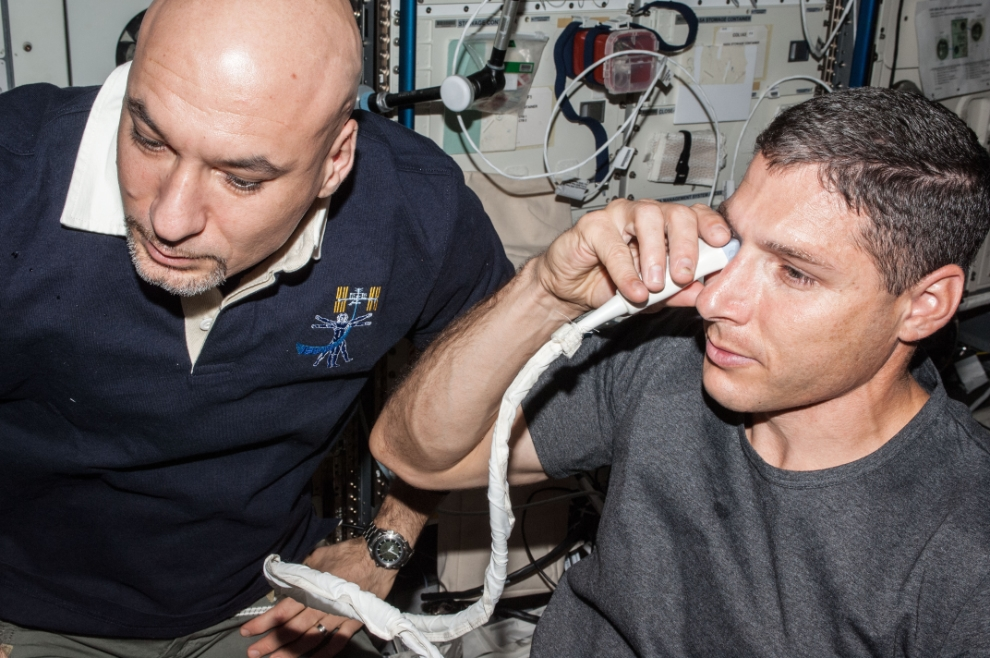NASA astronaut Michael Hopkins, Expedition 37 flight engineer, performs ultrasound eye imaging in the Columbus laboratory of the International Space Station. European Space Agency astronaut Luca Parmitano, flight engineer, assists Hopkins