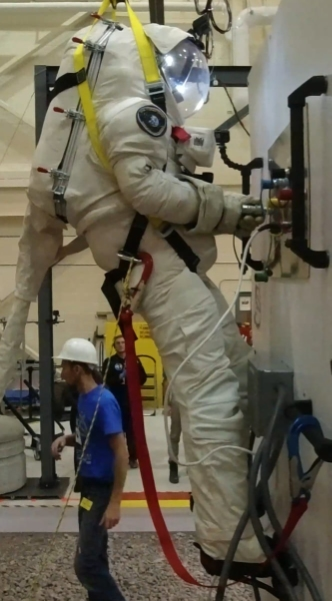 Project PoSSUM scientist-astronaut candidate Kyle Foster evaluates the functionality of analog fluid line and electrical line fittings in simulated microgravity conditions using PoSSUM's gravity-offset facility located at the Canadian Space Agency.